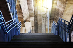 Concrete stairs are metal handrails under the bridge with orange Royalty Free Stock Photos