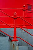 Concrete Stairs with Red Railing. Abstract architectural detail photo of a set of concrete stairs with bright red railings against a bright red wall royalty free stock photos