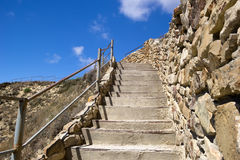 Concrete stairs up to hill and blue sky. Concrete stairs ascending to top of hill. Bright blue sky over the hill. Rock wall, handrail and dry grass. Close up stock photography