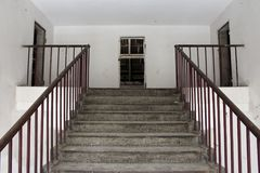 Stairway leading to attic of abandoned building. Concrete stariway with metal handrails leading to attic of dilapidated abandoned building with missing doors royalty free stock image