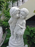A concrete statue of a young boy kissing a girl on the cheek. Royalty Free Stock Photo