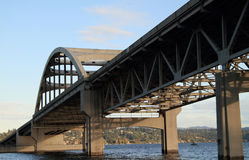 Concrete and steel arch bridge over water. A reinforced concrete and steel highway bridge over a lake stock images