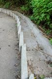 Concrete step flow for the flow of rainwater along a very steep asphalt walkway running down the hill Royalty Free Stock Photography