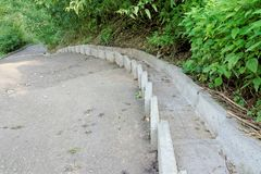 Concrete step flow for the flow of rainwater along a very steep asphalt walkway running down the hill Stock Image