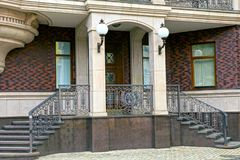 Concrete steps and iron forged handrails on the facade of a house with columns and lanterns on the street. Concrete steps and gray iron forged handrails on the royalty free stock image