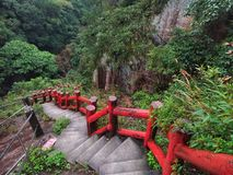 Concrete steps with red color handrail in a natural park of Ilan, Taiwan. Looks special and beaituful stock image