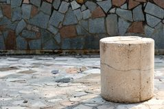 Concrete stone pillar on tile background. A low concrete stone pillar, on the right in the photo, against a background of a large stone tile texture, a mosaic, a royalty free stock image