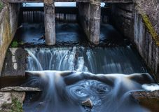 Concrete structure of the old river dam. Water blurred by long e stock image