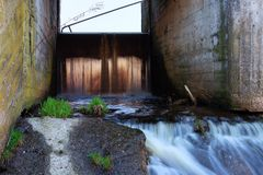 Concrete structure of the old river dam. Waterfall at sunset. Wa stock images
