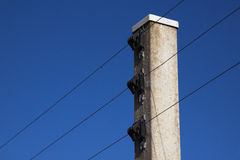 Concrete Support for Electric Fence Against Bright Blue Sky Stock Photography
