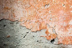 Concrete surface with the remains of orange paint and whitewash Royalty Free Stock Images