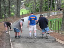 Concrete Teamwork. Laying newly concreted driveway and screening Stock Photos