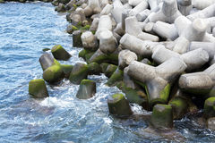 Concrete tetrapods form a ocean breakwater. Massive concrete tetrapods interlock to form a sea defense breakwater in the harbor at Funchal Madeira Stock Photo