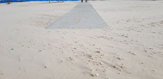 Concrete trail in the sand for disabled people goes from the sea royalty free stock photography