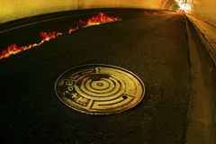 Concrete tunnel with fire and manhole. Photo of concrete tunnel with fire, manhole and beam lights at horizon Royalty Free Stock Photo
