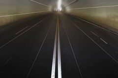 Concrete tunnel with no traffic. Photo of empty concrete tunnel with lines converging in the light Royalty Free Stock Image