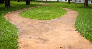 Concrete walk way surrounded by green grasses Stock Images