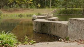 Concrete walkway through the river. Autumn daytime. Smooth dolly shot stock video footage
