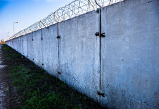 Concrete wall with barbed wire on top. Royalty Free Stock Photo