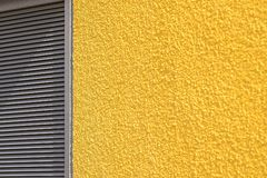 Concrete wall and blinds of yellow gray color Stock Photos