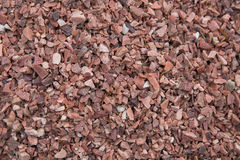 Concrete wall with brick-red pebbles Stock Photos