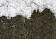 Concrete wall covered with snow. It can be used as a background for Christmas and New Year themes and more Stock Photography