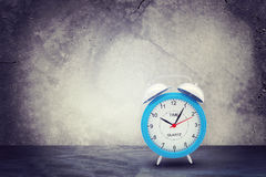 Concrete wall with fissure. Alarm clock in front Stock Images