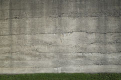 Concrete wall and grass. An old large concrete wall with a small strip of green grass at the bottom Royalty Free Stock Image