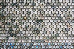 Concrete wall made of recycled plastic bottles. Bottle recycling: plastic bottles which have been set in concrete to form a bottle wall Royalty Free Stock Image