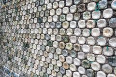Concrete wall made of recycled plastic bottles. Bottle recycling: plastic bottles which have been set in concrete to form a bottle wall Stock Image