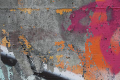 Concrete wall with peeling graffiti. Close-up view of a colorful peeling graffiti on a concrete surface royalty free stock images