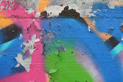 Concrete wall with peeling graffiti. Close-up view of a colorful peeling graffiti on a concrete surface royalty free stock photography
