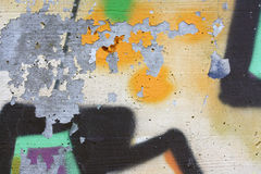 Concrete wall with peeling graffiti. Close-up view of a colorful peeling graffiti on a concrete surface royalty free stock photos