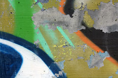 Concrete wall with peeling graffiti. Close-up view of a colorful peeling graffiti on a concrete surface stock image