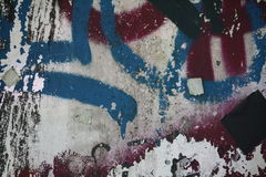 Concrete wall with peeling graffiti. Close-up view of a colorful peeling graffiti on a concrete surface royalty free stock image