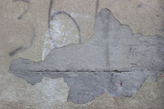 Concrete wall with peeling plaster. Gray wall with broken-off plaster Royalty Free Stock Photo