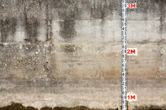 Concrete wall with ruler. Concrete wall with damp patches and with a ruler for measuring depth of water Royalty Free Stock Images