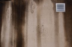 Concrete wall with small ventilating window covered with bad weather with streaks Stock Image