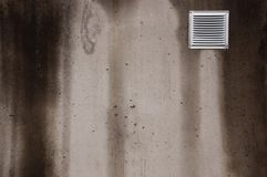 Concrete wall with small ventilating window covered with bad weather with streaks Stock Photo