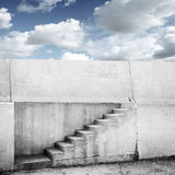 Concrete wall with stairway and blue cloudy sky. On background Royalty Free Stock Photography
