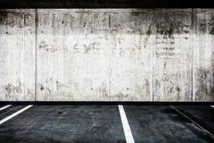 Concrete wall underground garage interior background texture. Parking garage underground interior background or texture. Concrete grunge wall and asphalt road Royalty Free Stock Photo