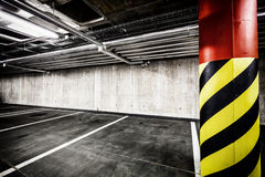 Concrete wall underground parking garage interior. Parking garage underground interior background or texture. Concrete grunge wall and column with warning sign Stock Photo