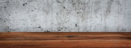 Concrete wall with wooden table. Gray old concrete wall with empty rustic wooden table for background decorations stock images