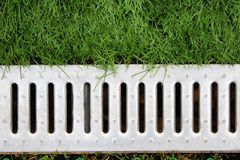 Concrete water drain or ditch on the road with green grass. Outdoor Stock Photography