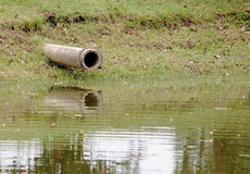 Concrete water duct pipeline near a pond Stock Photo
