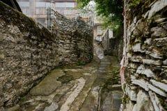 Concrete weg tussen oude steenmuren op helling stock foto's