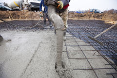 Concrete. Worker pouring concrete at construction site Stock Photos