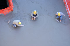 Concrete Workers. Three workers with one smoothing out freshly poured concrete Royalty Free Stock Photos