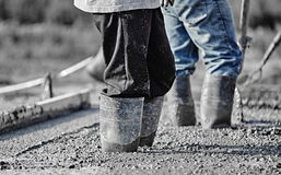 Concrete workers in heavy boots working in new wet concrete. Royalty Free Stock Photo