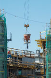 Concrete works. Charging hopper with concrete mix being transported by jib crane at the construction site Stock Photos